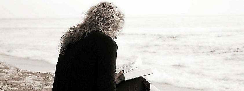 Eine Frau sitzt am Meer und liest ein Buch